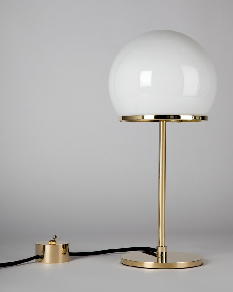 The Ingersoll table lamp by Remains Lighting has a simple yet elegant form. The single stem springs from a round base, disappearing into the cut-away section of a spherical white milk glass shade. This hand blown and cut glass is secured in place by