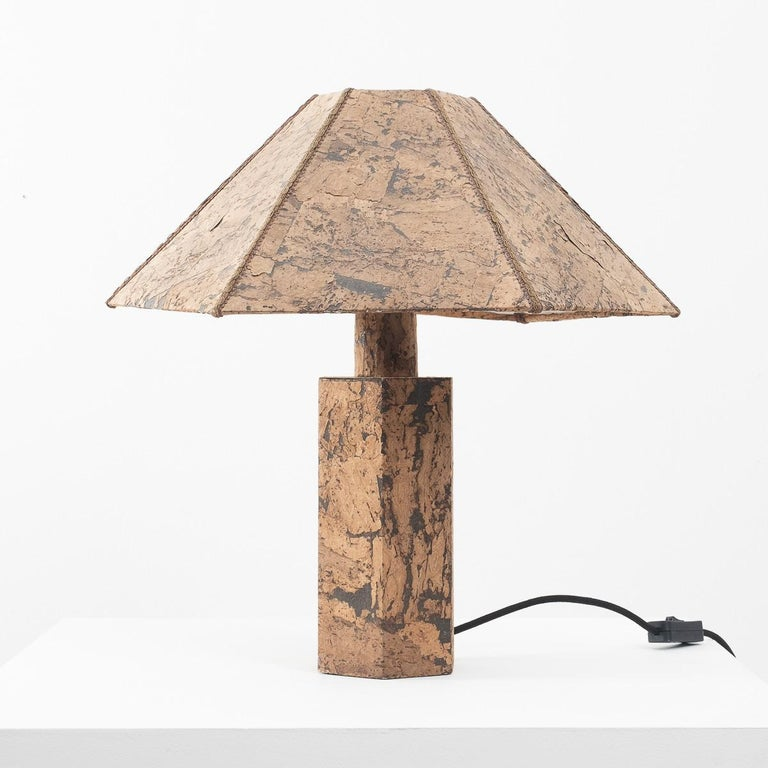 A pleasing hexagonal table lamp made from cork veneer. Redolent of a design by Wilhelm Zanoth and Ingo Maurer from 1974, which was larger with mitred edges. This one is more petite with upholstery braid masking its joins.   It is in very good