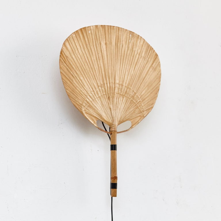 Appliqué 'Uchiwa III' created by Ingo Maurer for Design M.  In original condition, with minor wear consistent with age and use some small scratches as we show on the images, preserving a beautiful patina.  Bamboo, rice paper and black lacquered