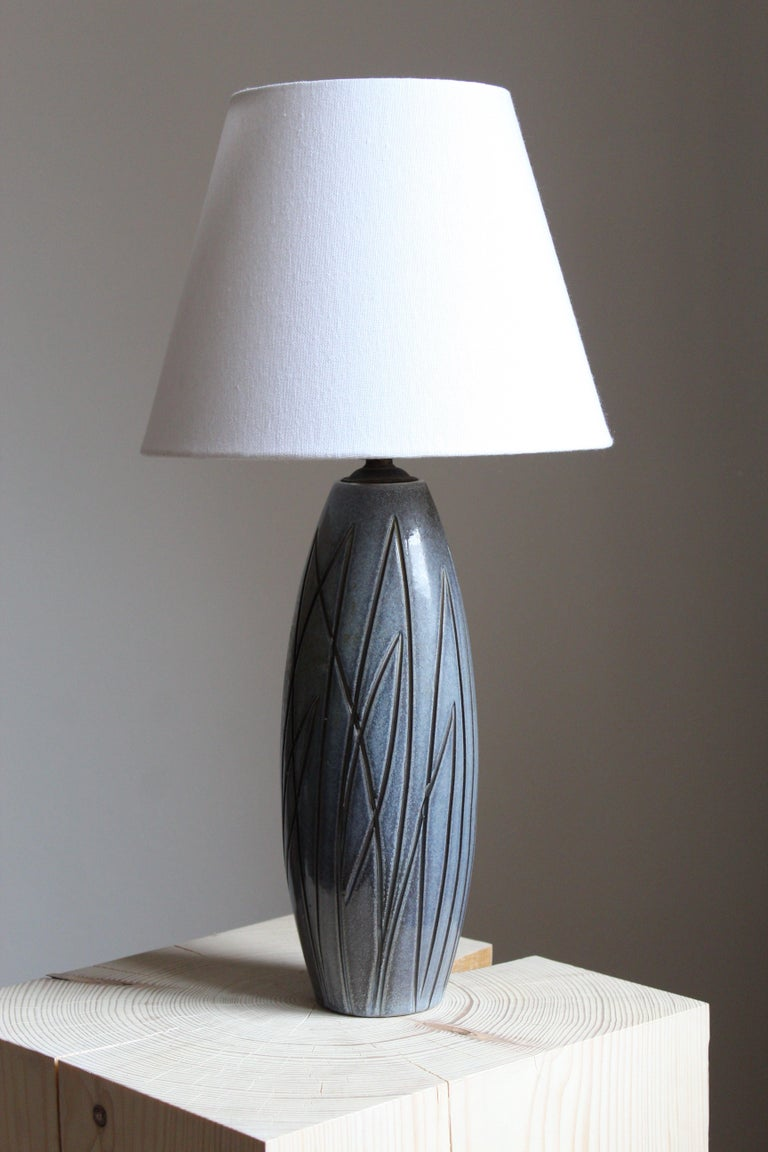 A table lamp, on a ceramic base designed by Ingrid Atterberg for Upsala Ekeby, Sweden, 1950s.  Sold without lampshade. Stated dimensions exclude lampshade. Illustrated lampshade can be included upon request.