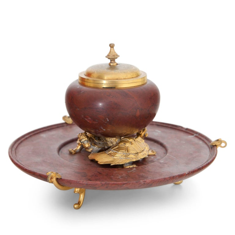 Inkwell out of red marble and gilt bronze by F. Barbedienne. The inkwell with a hinged lid stands on two bronze turtles and rests upon a three-legged marble plate. Maesures: Diameter inkwell barrel Ø 8 cm.