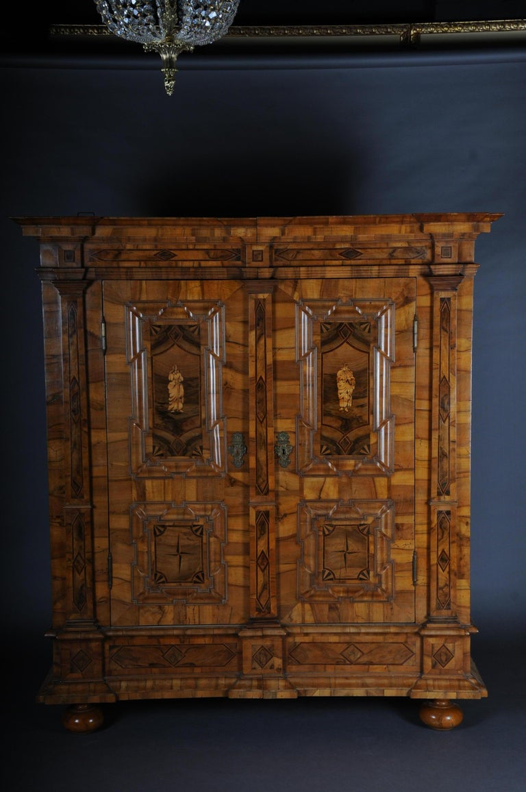 Highly interesting Baroque cupboard. Walnut on softwood. Straight frame base on printed ball feet. 2-door body. Original lock and wrought iron fittings.   (O-250).