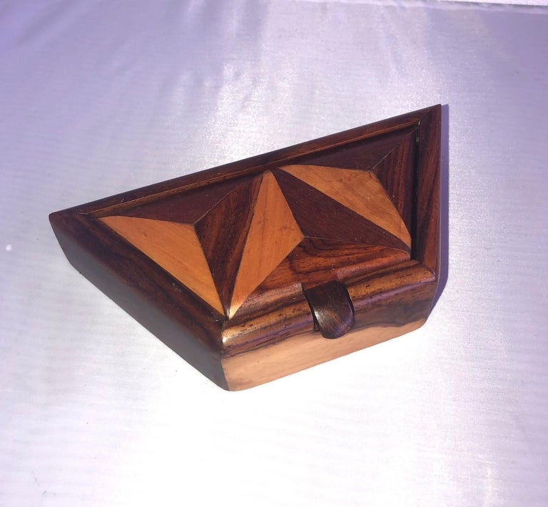Beautiful and unique handcrafted trinket box made of inlaid mixed woods (mahogany, walnut, burl wood, rosewood and maple), circa 1970s. The piece has a trapezoid shape and a attached lid that rotates up to open. The bottom of the box is felt lined.