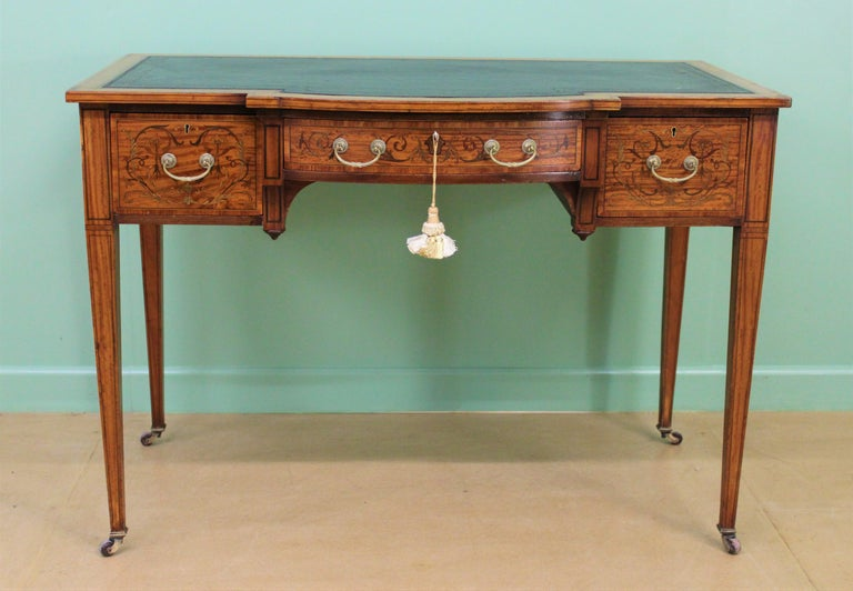 A fine quality inlaid satinwood writing table by the prestigious firm of Maple and Co of London. Dating to the late Victorian period and very well made with stunning satinwood veneers onto a solid mahogany frame. The top and drawer fronts are