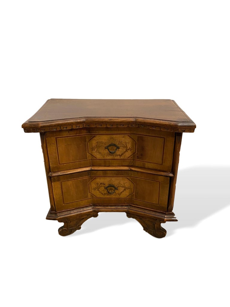 Inlaid walnut two-drawer side commode with concave block front, Italian, circa 1900, with shaped, molded top and half moon carved dentil molding below, with highly desirable concave blocked front, with inlaid satinwood geometrical central inlays