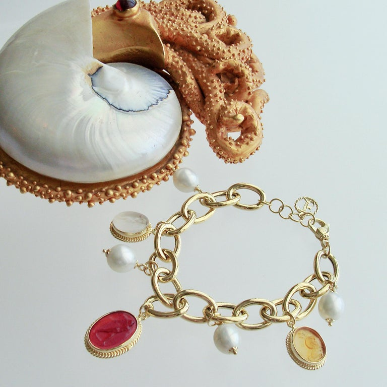 A unique gold vermeil link bracelet  has been artfully adorned with three Venetian glass intaglio charms which alternate with smooth and creamy freshwater pearls.  Each of the intaglio charms has been carefully set into a millegrain bezel which