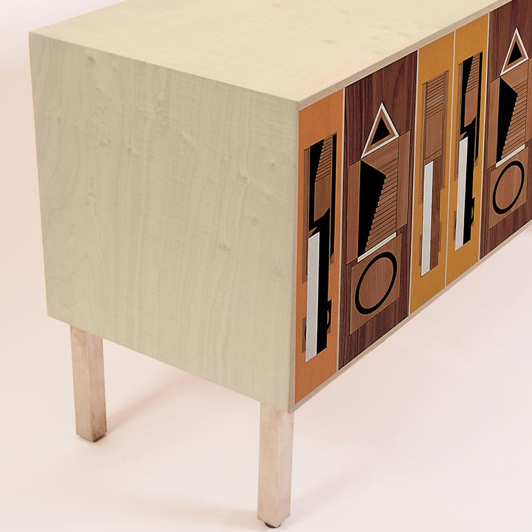 Retro motifs and soft grainy hues abound in this wood sideboard designed by Aldo Rossi and handcrafted by the skilled carpenters of Laura Meroni, using poplar and maple wood veneer. The doors open to reveal adjustable shelves, and an adjustable base