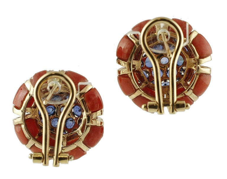 Faboulus pair of clip-on earrings realized in 14k rose gold structure. These earrings feature a central core studded with blue sapphires a round frame of beautiful red rubrum coral. The earrings are embellished with details in rose gold and