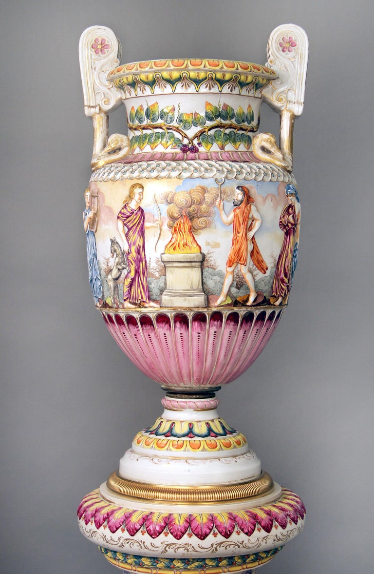 A large and interesting late 19th century gilt bronze and Italian Capodimonte porcelain vase and pedestal.  The vase with many different figures playing and holding instruments and weapons, centred around a flame, the top painted with vines,