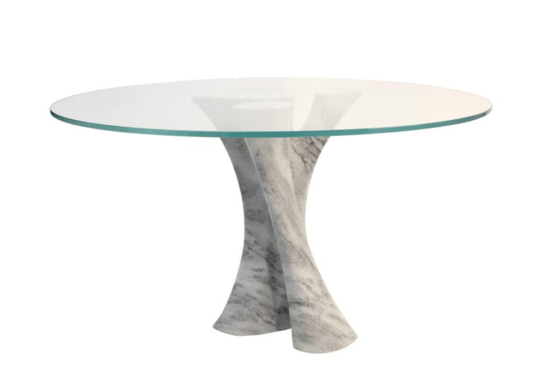 Dramatic leather topped dining table with solid carved stone pedestal base. Shown here in Georgia marble with a glass top, this piece is also available in a range of custom sizes, shapes, and materials. Choose from a selection of imported Italian