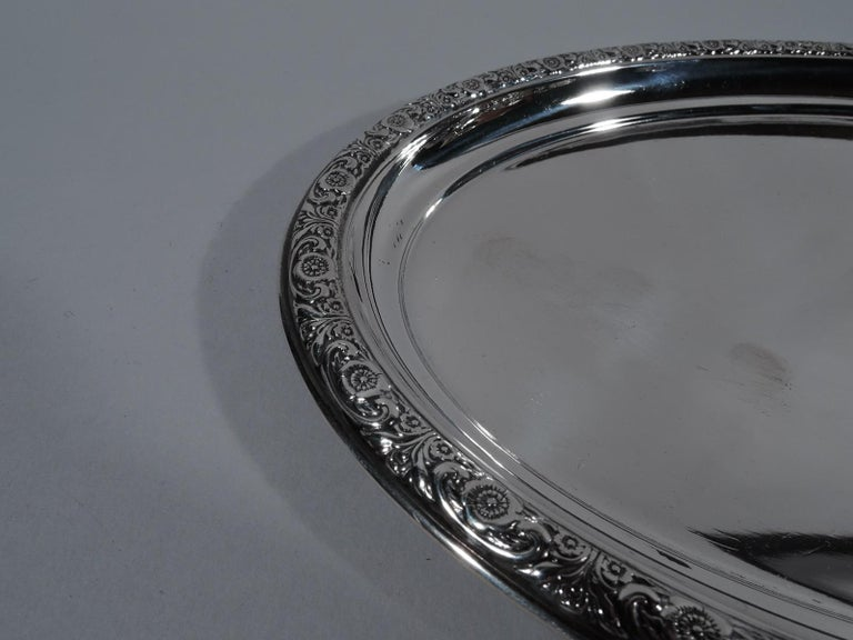 Prelude sterling silver tray. Made by International in Meriden, Conn. Oval. Rim has repousse flowers and scrolls. Fully marked including pattern name and no. W46. Weight: 5 troy ounces.