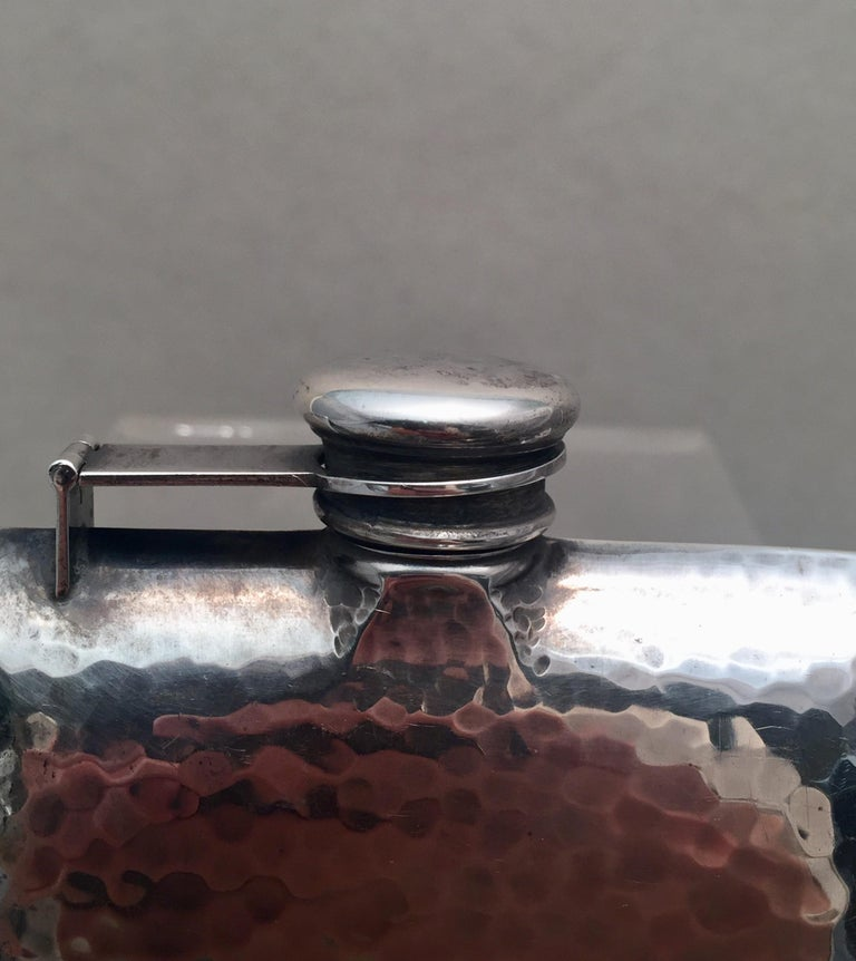 Sterling silver flask by International Sterling in the beautiful Arts & Crafts design, hand hammered. Open bottle by unscrewing cap. Measuring 6 inches tall and 4 inches wide. Bearing hallmarks as shown.   The International Silver Company was
