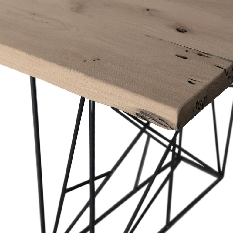 The iron base of the table creates a geometric weave that supports a top in solid Briccola oak. This material comes directly from the posts of the Venetian lagoon, used to signal the navigation limit to the boats. The oak, selected for its