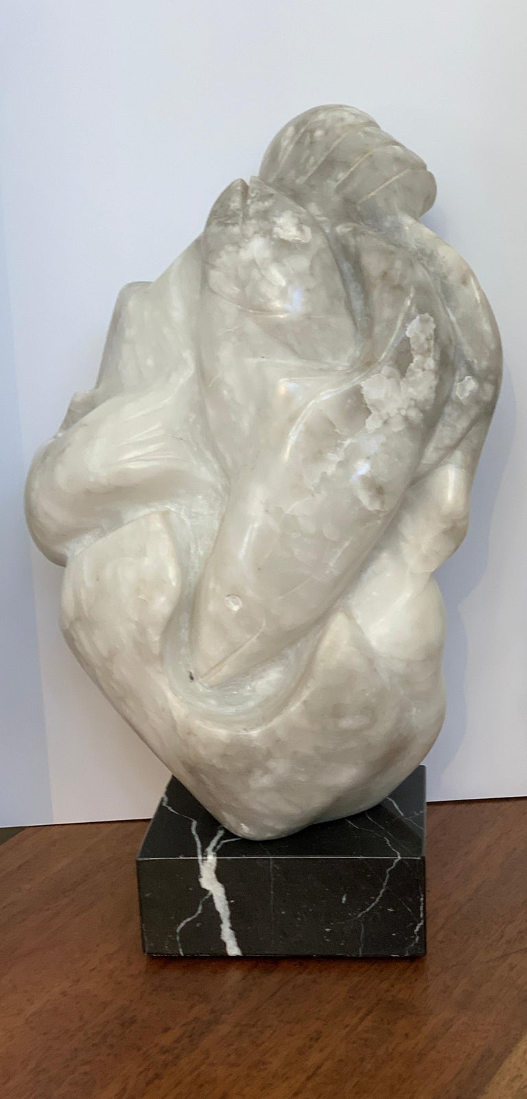 A lovely marble stone sculpture of intertwined salmon, likely an Inuit artist. It is mounted on a rod and black marble base so that it swivels. One corner of the bottom of the black marble base had a chip and has been smoothed. There are some nicks,