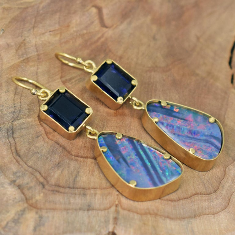 Two tier, hand forged 22k yellow gold dangle earrings featuring Emerald / Octagon cut, deep violetish-blue Iolite (7.7 cttw) and beautiful Australian Boulder Opal (18.6 cttw) gemstones. Dangle earrings are 2.25 inches in total length, including