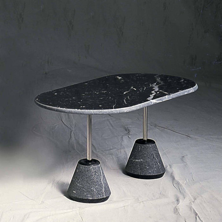 The structure of this exclusive coffee table designed by Achille Castiglioni for UpGroup is both light and robust, as it plays on the idea of balance and tension, giving the design a dynamic quality. The striking black Marquinia oval top rests on a
