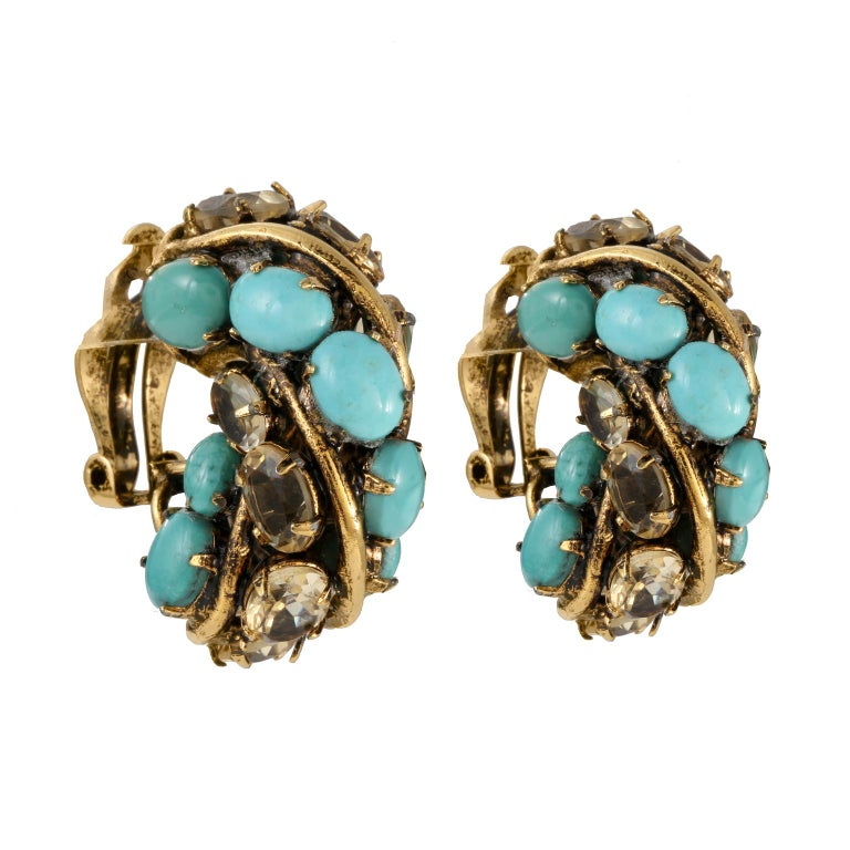 These Iradj Moini Turquoise and Crystal Earrings are in excellent condition.  Turquoise and crystal stones set in in gold tone metal.  Clip on closure.  Pouch or box included.