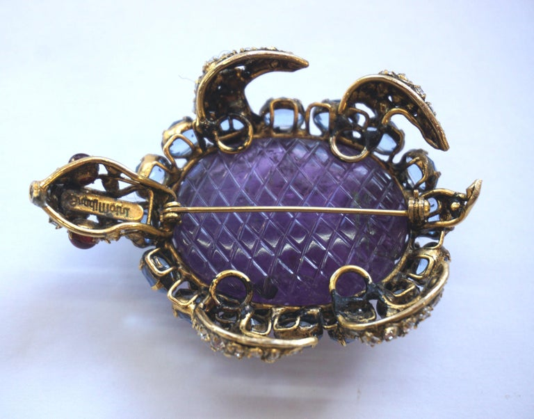 Stunning statement piece incorporating of carefully carved amethyst, blue topaz, rubies (eyes) and crystals and gold toned base metal, circa 1980. Signed on back. Size: 3.00