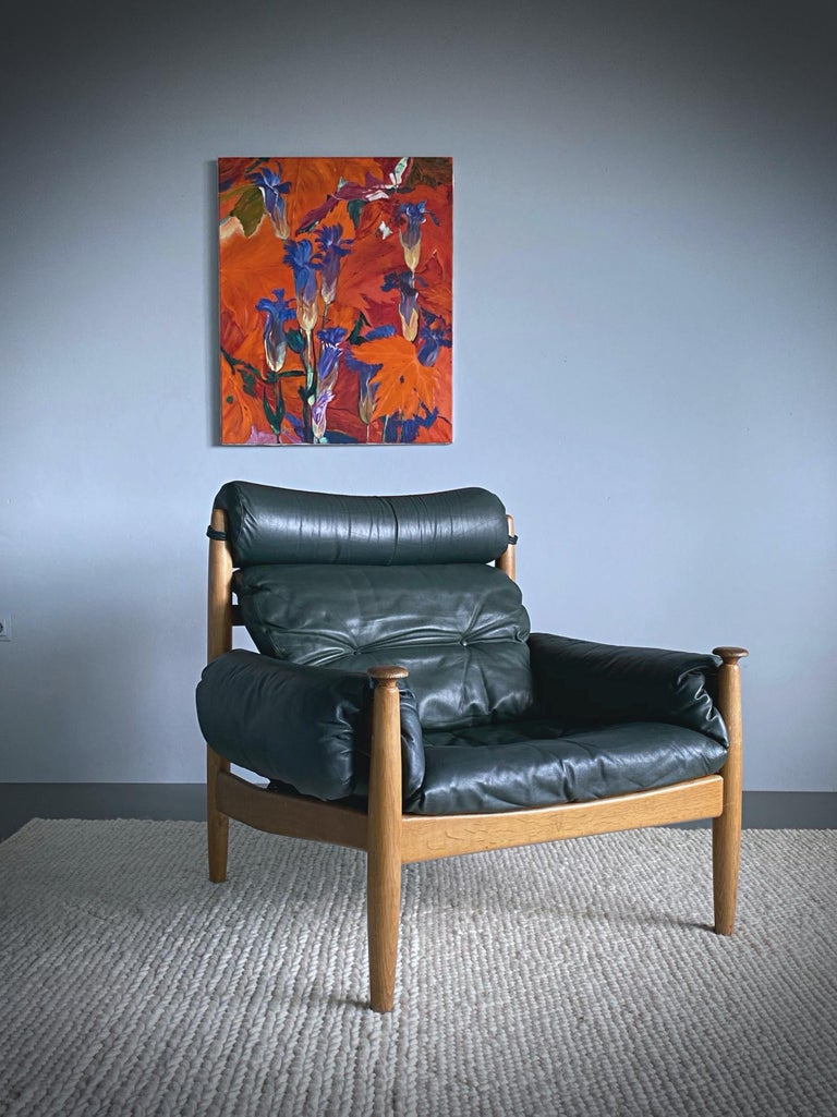 Timeless 1960s leather lounge chair designed by Eric Merthen for IRE Möbler in Sweden. This armchair is made of stained oakwood with dark green leather pillows. The chair has been freshly cleaned by our upholstery. Very good condition with nice