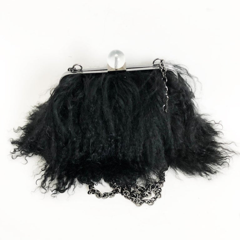 Iris Apfel Extinctions Black Mongolian Lamb Fur Bag. Features a chain strap for shoulder wear or can be stowed in the bag for use as a clutch. Lined in blue grosgrain fabric. Fastens with clear bubble clasp. Preowned with minimal signs of prior