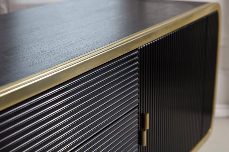 This stylish credenza is constructed from blackened oak and is fronted with Corian doors and drawer which are offset by liquid and solid brass. Interiors are lined with Alcantara.
