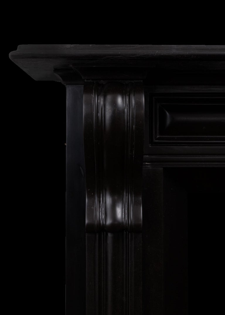 A black Kilkenny marble fireplace surround. This fireplace is in the early 19th century Irish Regency style. It has cushion moulded panels running into corbels, tapering aperture and a deep moulded shelf. A design which was popular in Ireland