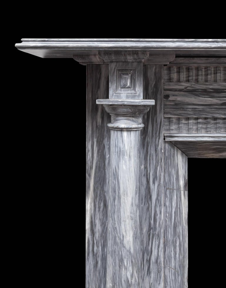 An Irish antique Regency grey Bardiglio marble fireplace. The moulded shelf sits above projecting end-blocks carved with recessed panels, these are supported by full rounded Tuscan columns standing freely in front of plain pilasters. The frieze