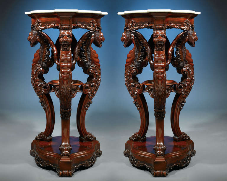 This pair of striking Irish rosewood pedestals with marble tops stand well above four feet tall, making a truly grand statement. The rich rosewood is lavishly carved with dramatic scrollwork and three exotic winged lion supports. These lions each