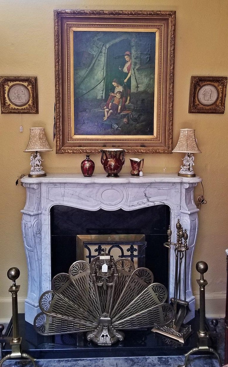 20th century Irish, complete white marble fireplace, in 18th century style, with black granite and brass plinth and hearth insert. Perfect for a bedroom! The two side pillars are carved to resemble scrolling columns. The centre portion is an