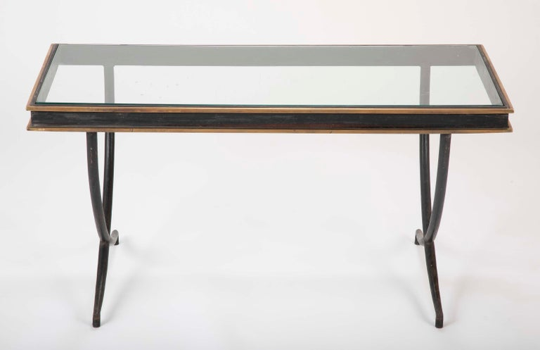 A beautiful iron and polished bronze glass top coffee table in the manner of Andre Arbus.