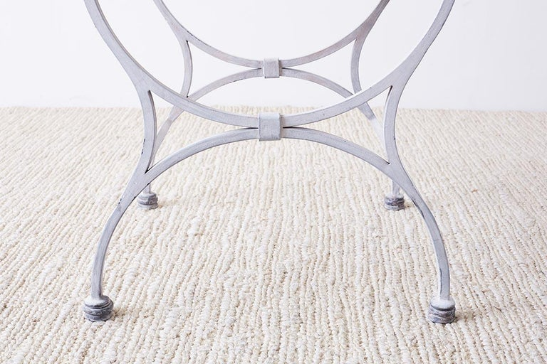 Distinctive iron and stone patio or garden drink table mode in the neoclassical taste. Features a thick molded stone top with a beveled edge. The iron frame has a reeded edge and is supported by curved curve style legs conjoined on top and bottom.