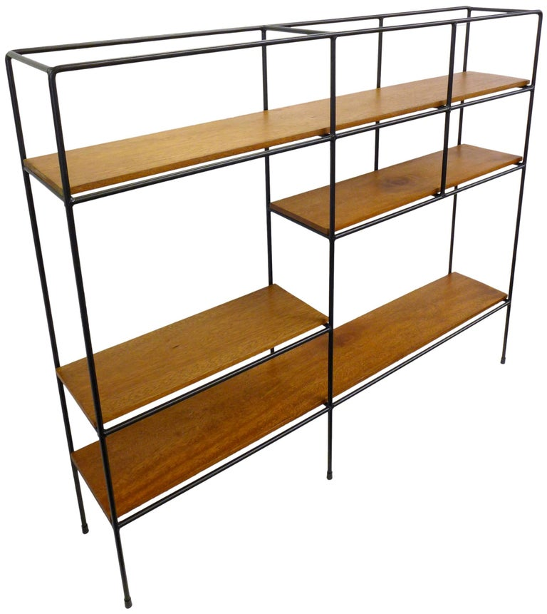 A fantastic, free-standing iron and wood shelving unit by Muriel Coleman.  An asymmetrical, welded- and wrought-iron frame with variously-sized display areas and 4 wood shelves.  Impressive scale and proportion; open all round and could be used as a