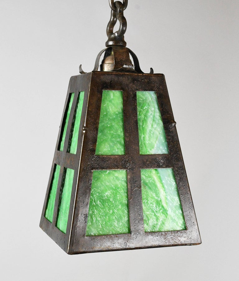 This is a beautiful and petite iron pendant. It has green slag glass for the shade. It is influenced by the Arts & Crafts style, and the design is eye-catching yet not overly complex. This fixture would fit in your space very well if you're an Arts