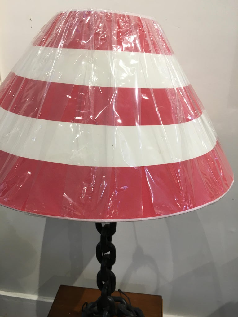 Old iron ship's chain welded together to create a table lamp.  Red and white striped shade complete the look.  One standard base light bulb and newly wired.  Shade is 22 inches wide at the bottom and 10 inches high.  Overall height is 34 inches.