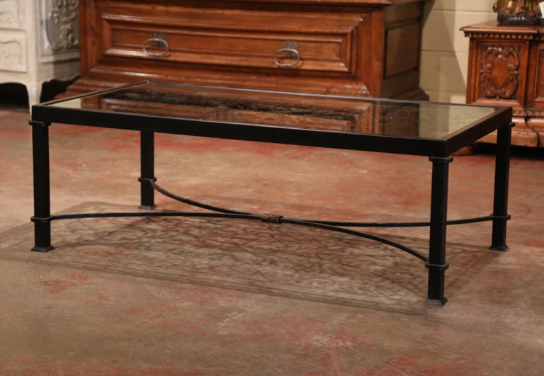 Decorate a den or a formal living room with this iron coffee table; built using an ornate, antique gate from France, circa 1850, the unique table features four square legs decorated with a bottom curved stretcher. The top has intricate scroll motifs
