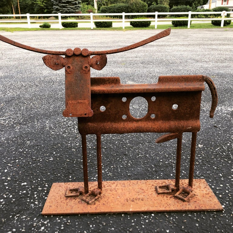 Signed Heiss iron cow sculpture. Junkyard style art by famous artist Heiss. Used pieces of scrap metal designed to form a sculpture. Great as a doorstop.
