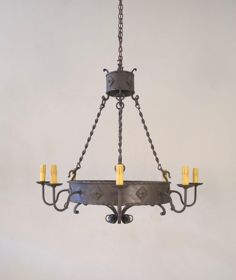 Our 8-light forged iron ring chandelier with Clavos and rope details. Made by chandelier. 8 medium base bulbs up to 60 watts/socket. UL approved, chain and canopy included.
