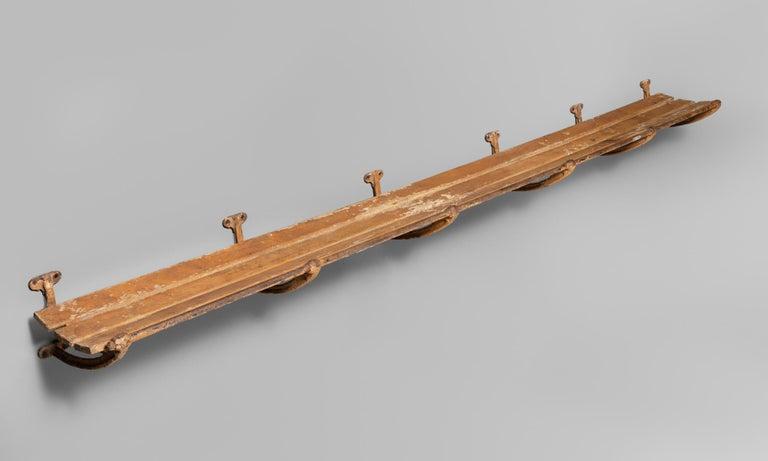 Iron and wood luggage rack, England, circa 1910.  Wall-mounted storage rack made of iron and plank wood.