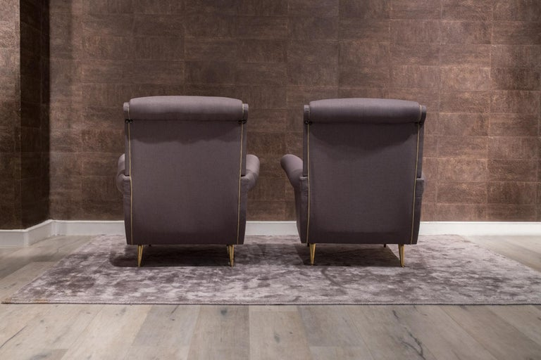 Italian midcentury Classic sculptural armchairs designed by I.S.A. Bergamo. The backs feature slightly rolled arms, supported on gilded curved brass legs. These generously proportioned chairs have been entirely reupholstered. ISA Bergamo vintage