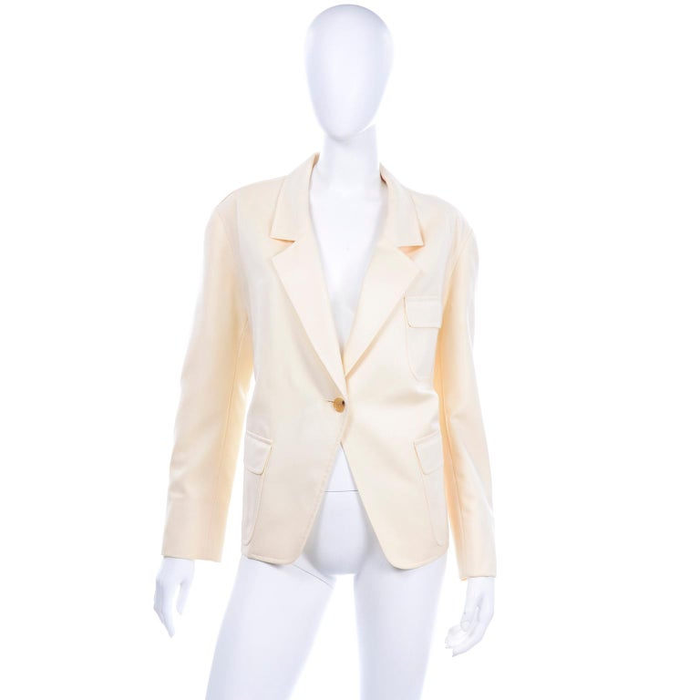 Vintage Isaac Mizrahi 100% Pure New Wool cream blazer. This boxy jacket closes with one light tortoise button and has flap front pockets, a breast pocket, and shoulder pads. The blazer is fully lined with small buttons on the sleeves.Labeled size