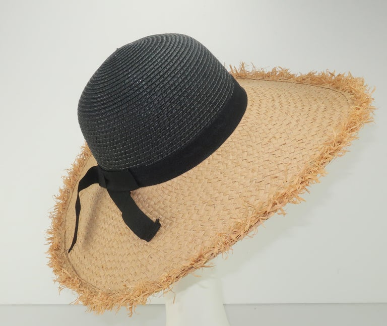 Isaac Mizrahi paper straw hat in a combination of natural and black with a black grosgrain ribbon band.  The fringed edges to the brim lends the hat a vintage 'tiki' look perfect for beach wear.   CONDITION Good previously owned condition.  No