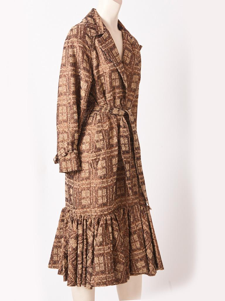 Isabel Toledo, patterned jacquard, in neutral tones of browns and beige with copper accents belted trench style coat. Details include, a gathered flounce at knee extending to the hem, a deep inverted  center back pleat, and wide lapels. Coat is