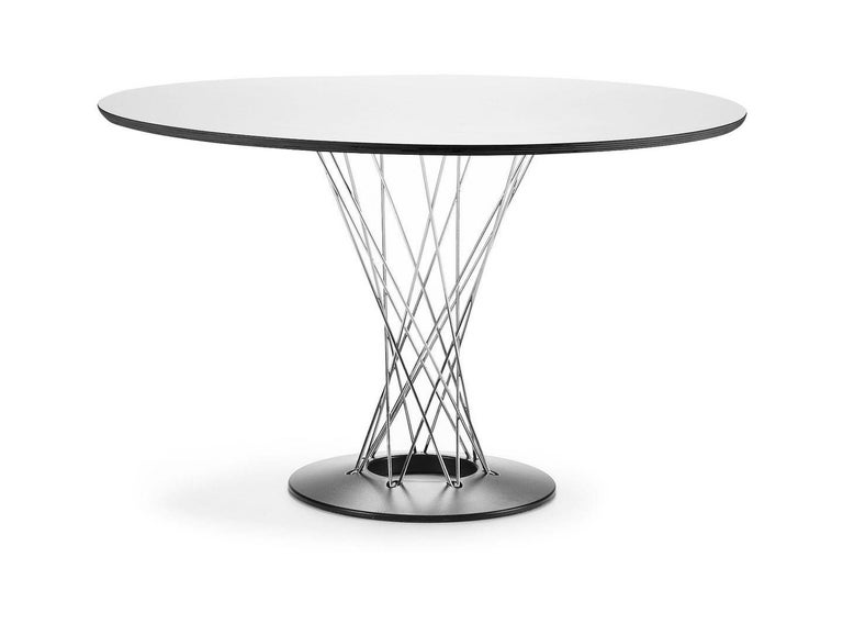 Table designed by Isamu Noguchi in 1957. Manufactured by Vitra, Switzerland.  Featuring a pedestal base made of chrome-plated rods, the Dining Table (1954/55) by artist and designer Isamu Noguchi is one of the most elegant dining tables in the