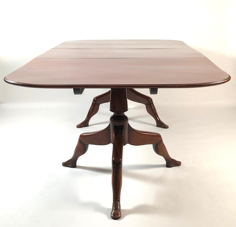 An unusual mahogany extension dining table from the Isle of Man, with rich, deep color, the rectangular top with rounded corners and bullnose edge, supported by two pedestals raised on tripod legs, carved as human legs wearing carved brogue shoes,