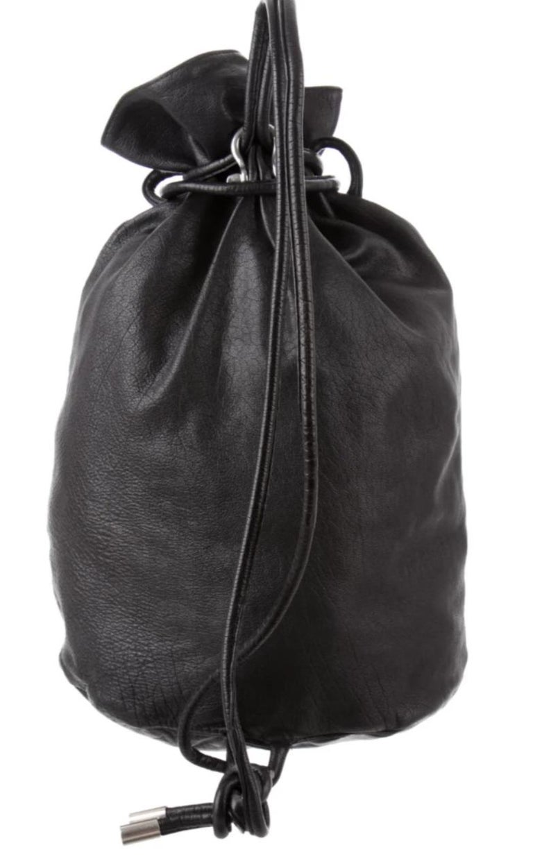 1980s Black leather vintage Issey Miyake backpack with silver-tone hardware. Two straps. Two front pockets. Drawstring closure. 18.25