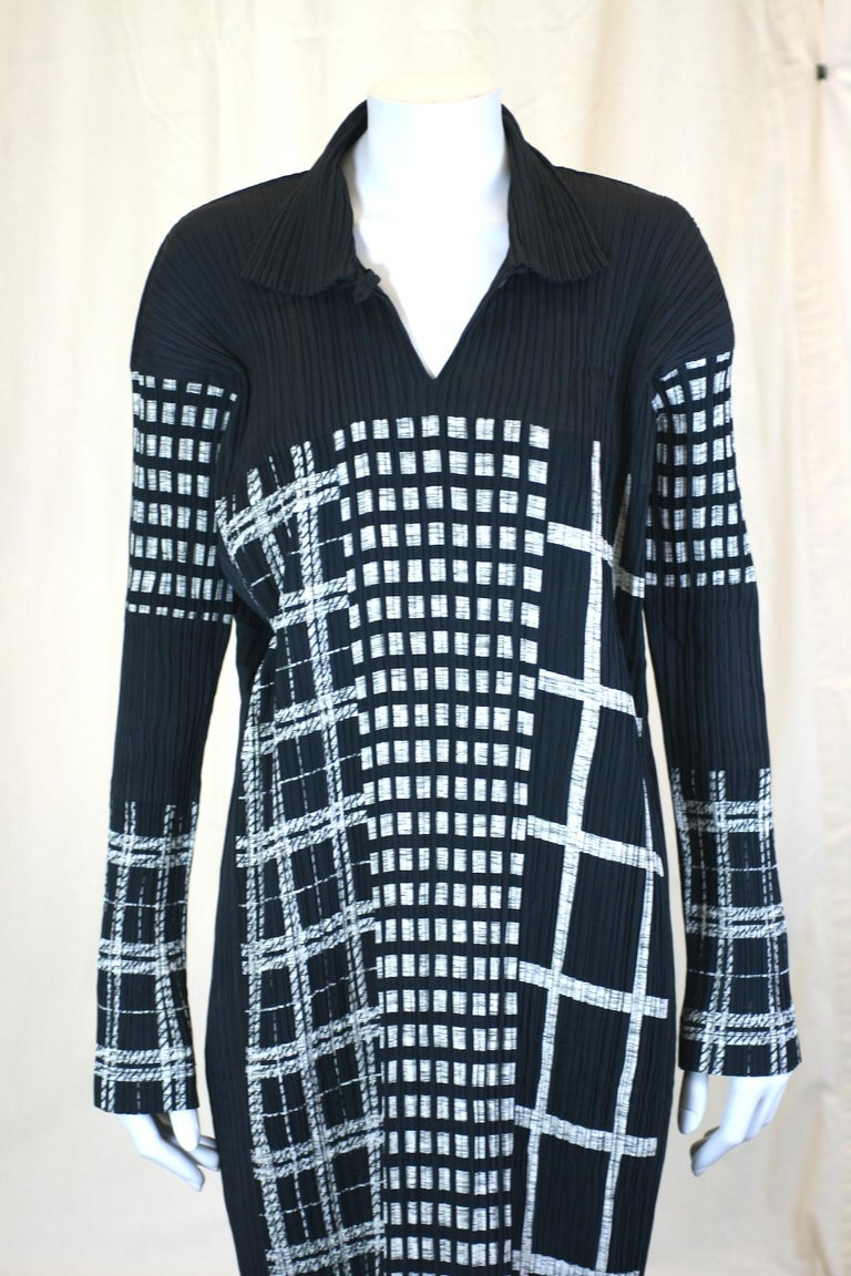 Issey Miyake Graphic Black White Dress in signature pleats. The various patterns look like a night time cityscape. Pullover style with open slash collar with long, lean silhouette. Size Small. Length 50