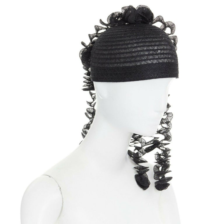 ISSEY MIYAKE PLEATS PLEASE Black raffia straw knit. Round pullover cap. Draped spiral dangling strips. Statement party hat. Grosgrain trimmed along lining. Made in Japan.  CONDITION New without tags.