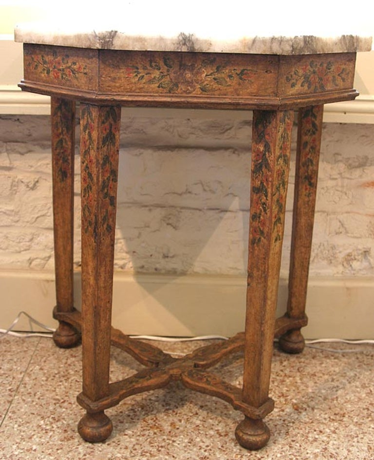 An Italian Baroque painted console with the original grey and white marble top. The sides, four legs and X-shaped stretcher are detailed with flowers and leaves.