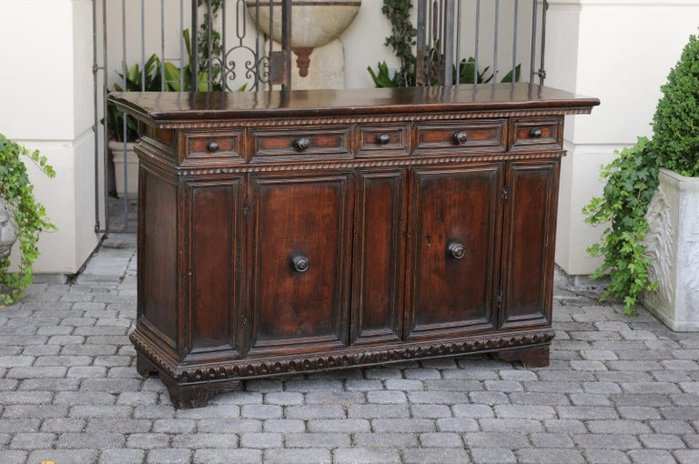 An Italian walnut credenza from the early 19th century, with five drawers, two doors and carved accents. Born in Italy during the early years of the 19th century, this exquisite walnut credenza features a rectangular top adorned with scooped