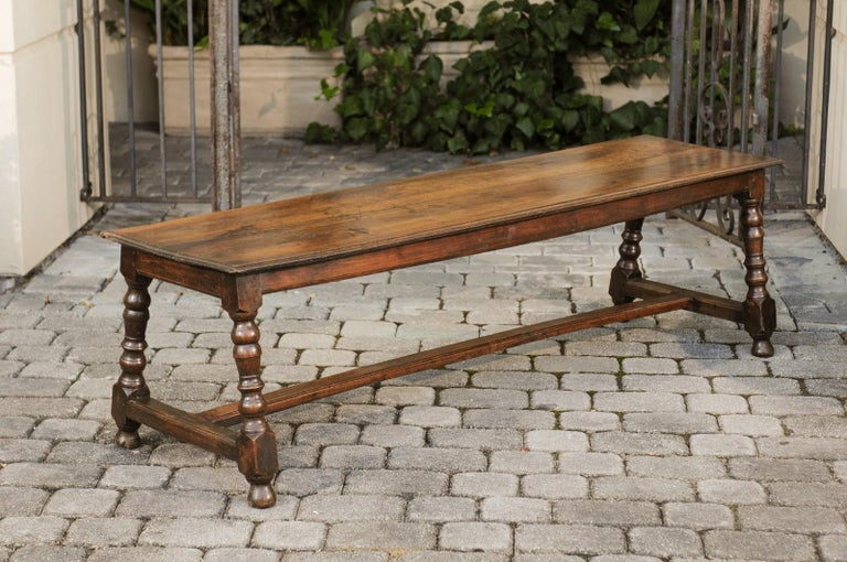 An Italian walnut bench from the early 19th century, with turned legs and cross stretcher. Born in Italy during the early years of the 19th century, this walnut bench features a rectangular top sitting above four splaying turned legs connected to